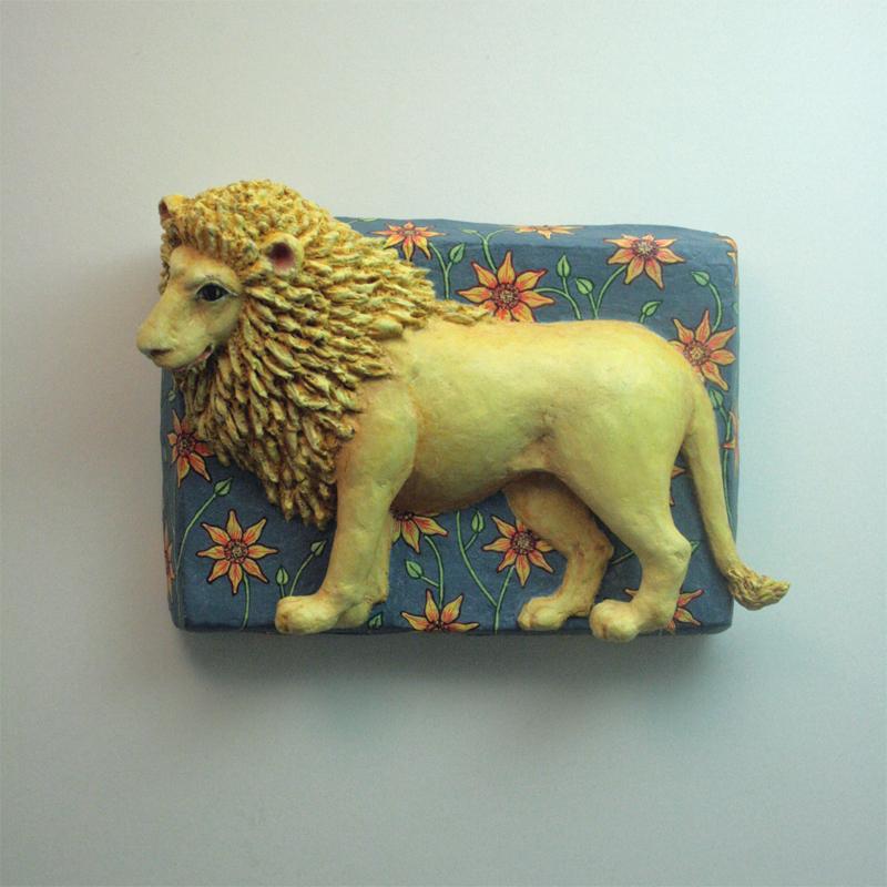 ein Löwe, zu sehen von der linken Seite, dreht den Kopf mit gewaltiger Mähne leicht nach vorne. Auf blauem Grund mit gelb-roten Blüten