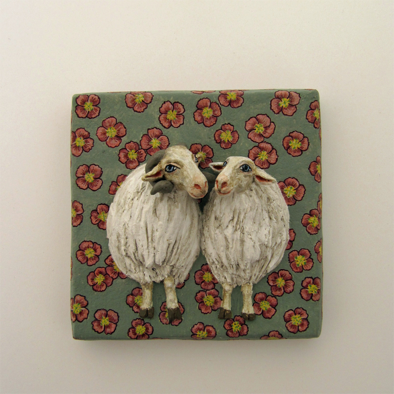 zwei Schafe, ein Widder und ein weibliches, die sich offenbar mögen, die Köpfe einander zugewandt. Auf matt graugrünem Grund mit rot-gelben Blüten.